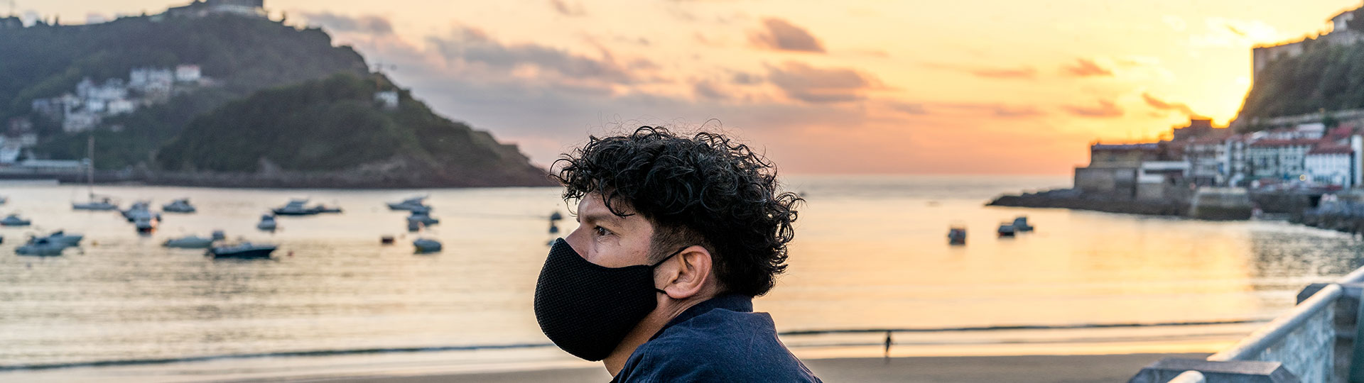 Boy with mask looking at the sunset on La Concha beach, San Sebastian